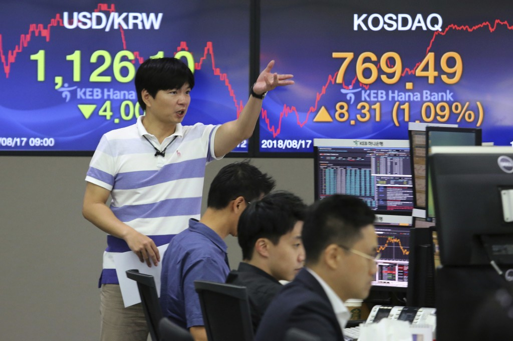 A currency trader gestures at the foreign exchange dealing room of the KEB Hana Bank headquarters in Seoul, South Korea, Friday, Aug. 17, 2018. Asian ...