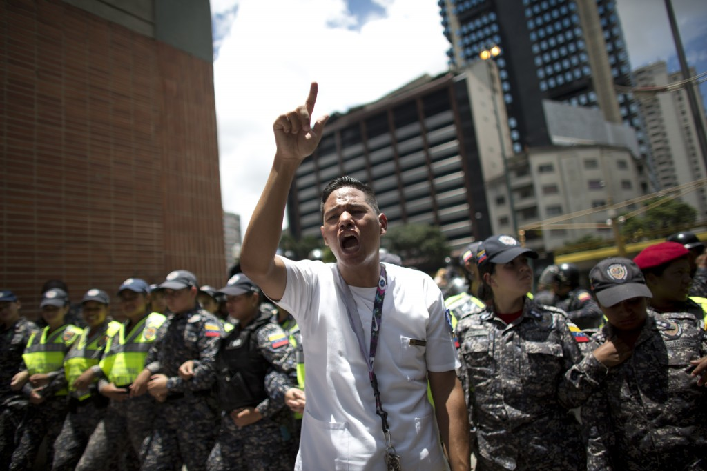 A nurse shouts anti-government slogans during a protests against the government of President Nicolas Maduro, in Caracas, Venezuela, Thursday, Aug. 16,...