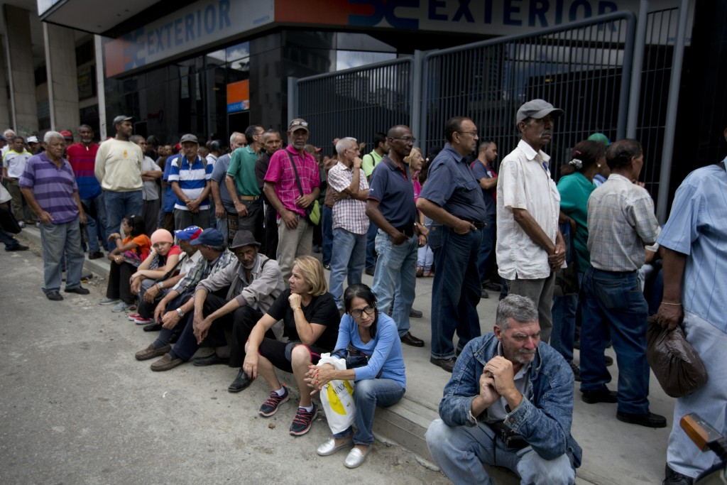 People lineup outside of a bank to get some cash in Caracas, Venezuela, Thursday, Aug. 16, 2018. If multiple exchange rates and cash shortages driven ...