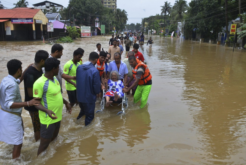 In this Thursday, Aug. 16, 2018 photo, an elderly woman is evacuated towards safer area in Thrissur, in the southern Indian state of Kerala. Rescuers ...