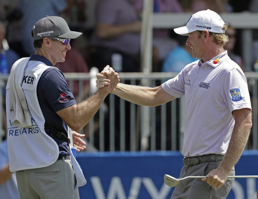 Brandt Snedeker, right, celebrates with his caddie after making a birdie putt on the ninth hole during the first round of the Wyndham Championship gol...