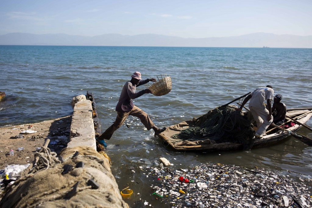 In this Aug. 13, 2018 photo, a fisherman jumps on to his wooden boat, joining his mates as they head out to the sea from Port-au-Prince, Haiti. (AP Ph...