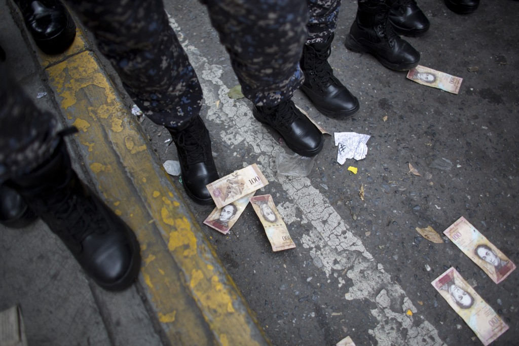 One hundred Bolivar bills lay on the ground close to the boots of several police officers, after they were thrown by protesters during a protest again...