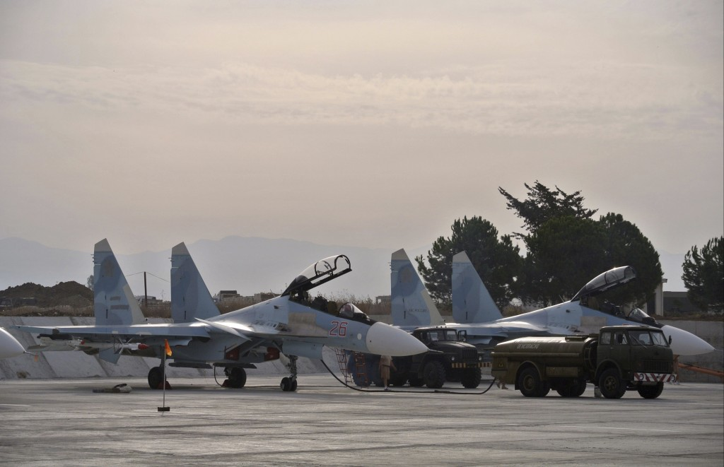 FILE - In this Oct. 22, 2015 file photo Russian fighter jets are parked in preparation for combat action at Hemeimeem airbase, Syria. Merkel and Putin...