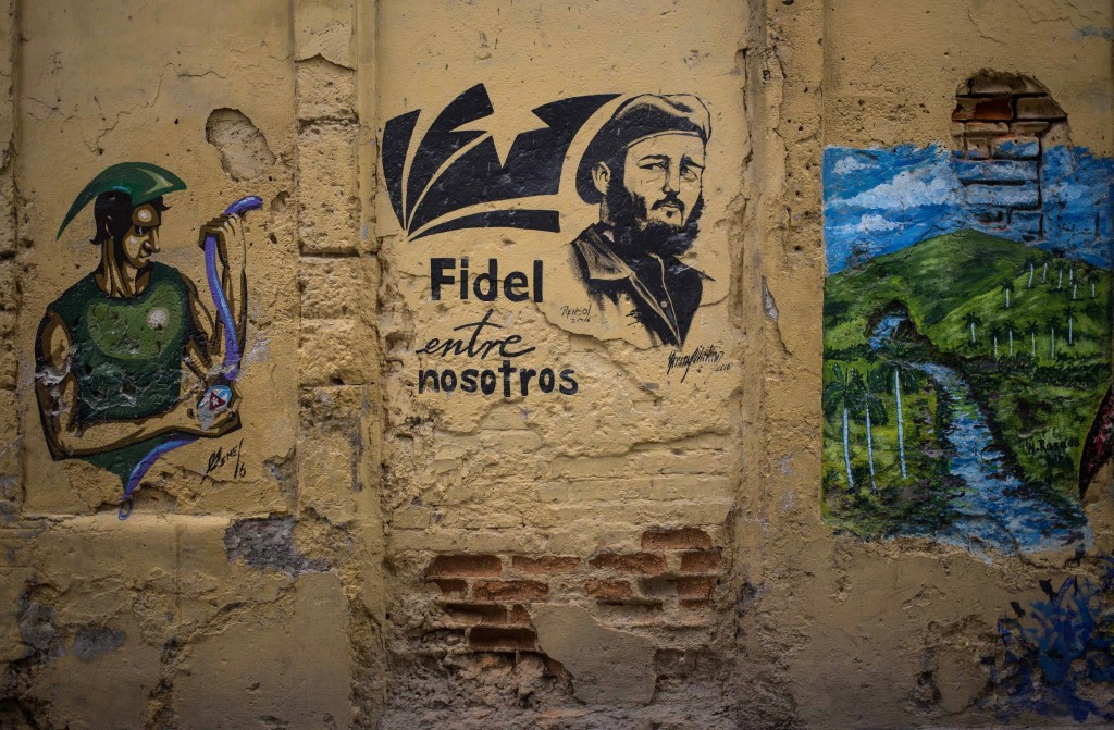 """In this Aug. 13, 2018 photo, she Spanish message: """"Fidel is among us"""" covers a wall next to an image of the late leader in Havana, Cuba. Cuba's new co..."""