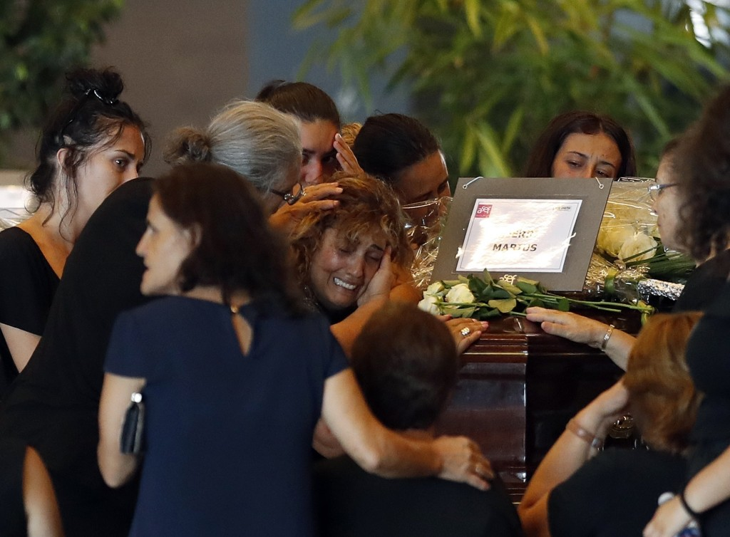 A woman is comforted as she mourns a victim of a collapsed highway bridge, at the Fiera di Genova exhibition center, where some of the victims are lai...