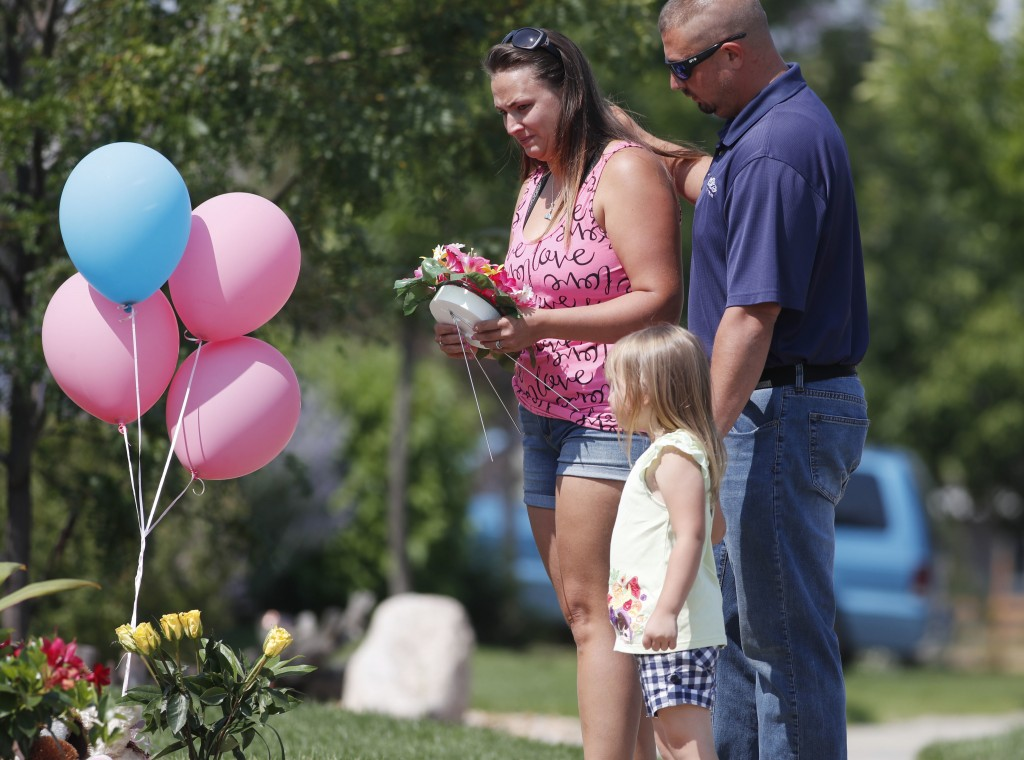 Ashley Bell, left, is consoled by her husband, Steven, and 4-year-old daughter Liberty as the woman places a tribute outside the home where a pregnant...