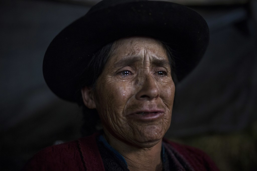 In this Aug. 15, 2018 photo, Antonia Yupanki Tineo, 58, cries near the coffin of her uncle Alejandro Tineo, who was killed by Shining Path guerrillas ...