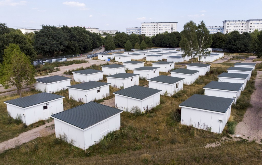 In this Aug. 16, 2018 photo houses originally built for refugees sit on the site of a former refugee center in Hamburg, Germany. The boxy houses, 28 s...