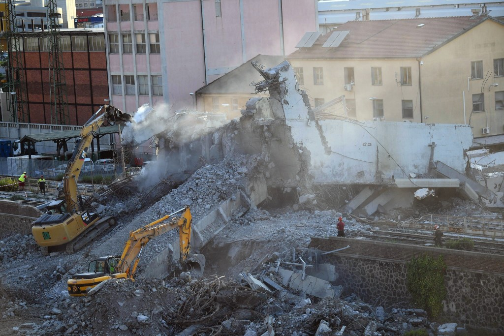 Firefighters remove debris of the collapsed Morandi highway bridge in Genoa, Italy, Thursday, Aug. 16, 2018. Italian authorities have lowered the deat...