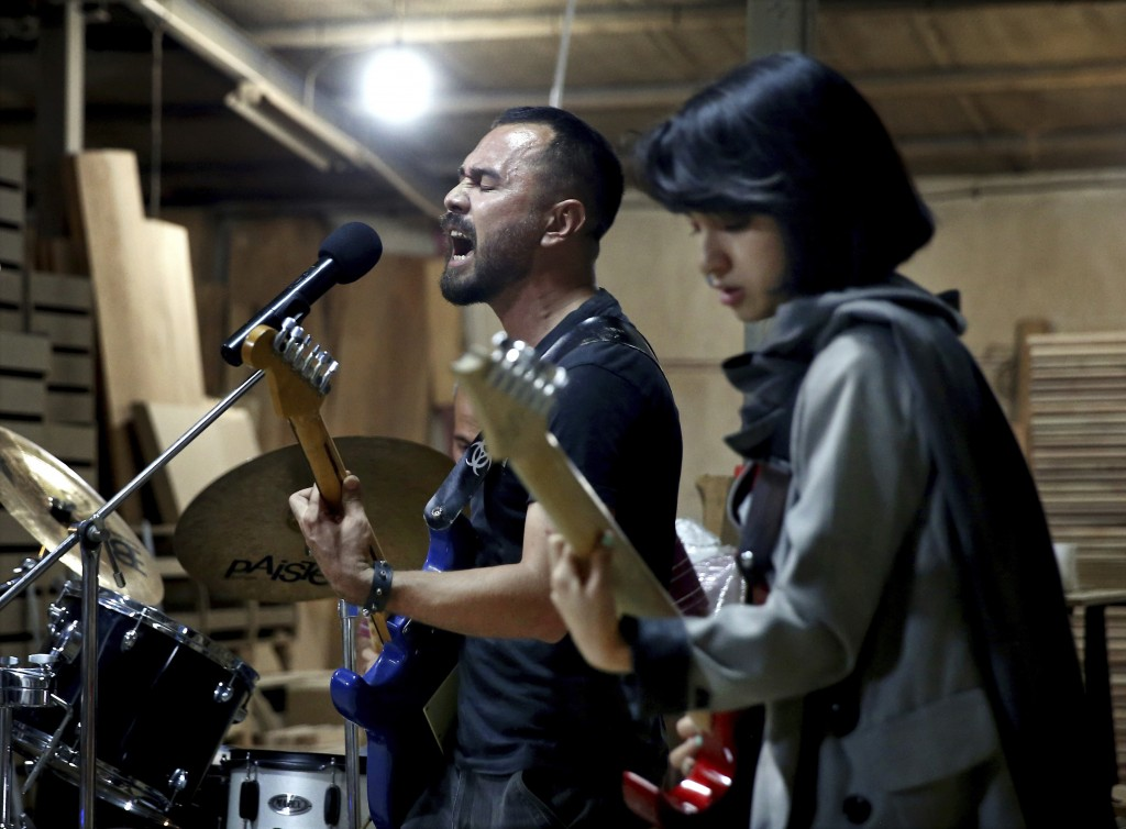 In this July 20, 2018 photo, members of the rock band Arikayn, Afghan musicians Hakim Ebrahimi, center, and Soraya Hosseini, play at a furniture works...
