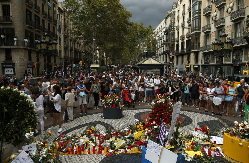 People gather next to at floor mosaic by Catalan artist Joan Miro where the van driven by the attacker stopped in Barcelona, Spain, Friday, Aug. 17, 2...
