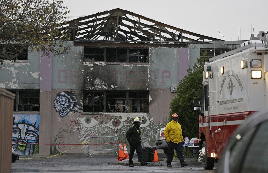 FILE - In this Dec. 7, 2016 file photo, Oakland fire officials walk past the remains of the Ghost Ship warehouse damaged from a deadly fire in Oakland...