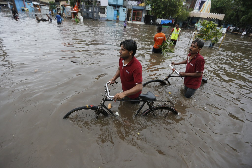Indian men push their cycles past floodwaters after heavy rainfall in Ahmadabad, India, Friday, Aug. 17, 2018. India receives its annual rainfall from...