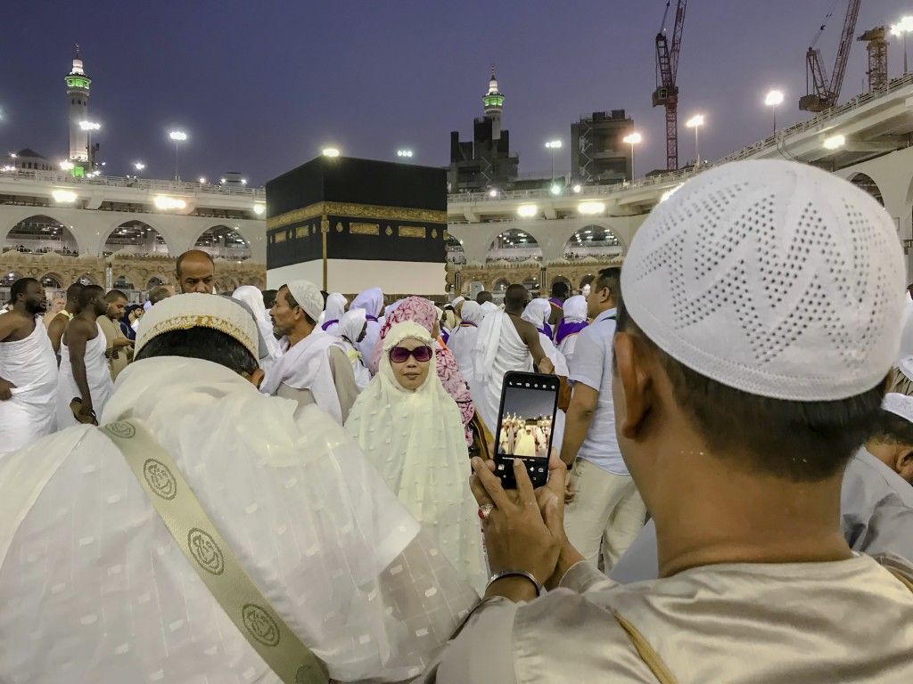 A Muslim pilgrim takes a photograph of his relative near the Kaaba, the cubic building at the Grand Mosque, in the Muslim holy city of Mecca, Saudi Ar...