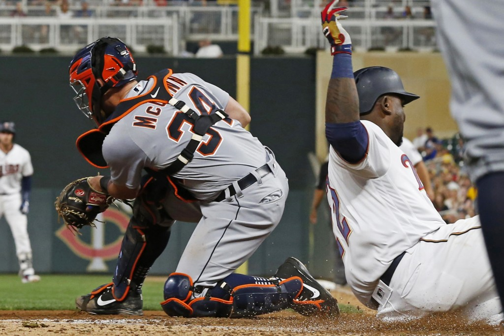 Minnesota Twins' Miguel Sano, right, beats the throw to Detroit Tigers catcher James McCann to score on a two-run single by Mitch Garver during the si...