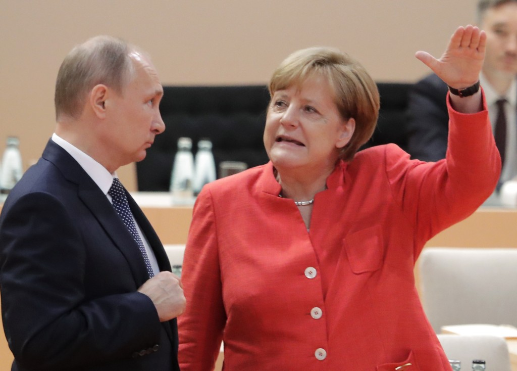 FILE - In this July 7, 2017 file photo Russian President Vladimir Putin, left, talks with German Chancellor Angela Merkel prior to the first working s...