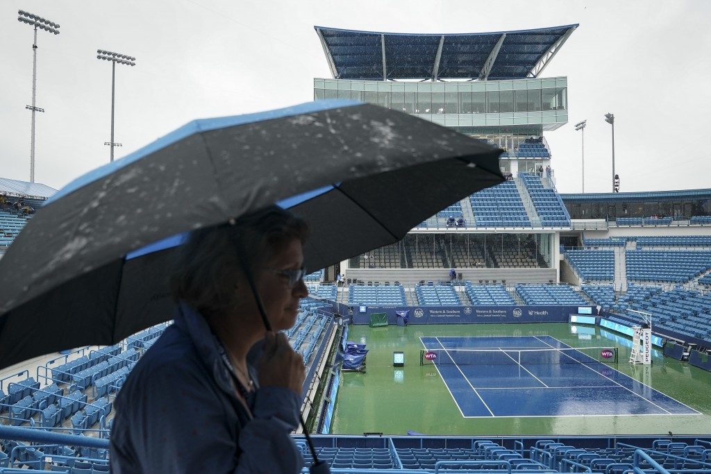 An atendee shelters from the rain at center court during a delay at the Western & Southern Open tennis tournament, Thursday, Aug. 16, 2018, in Mason, ...