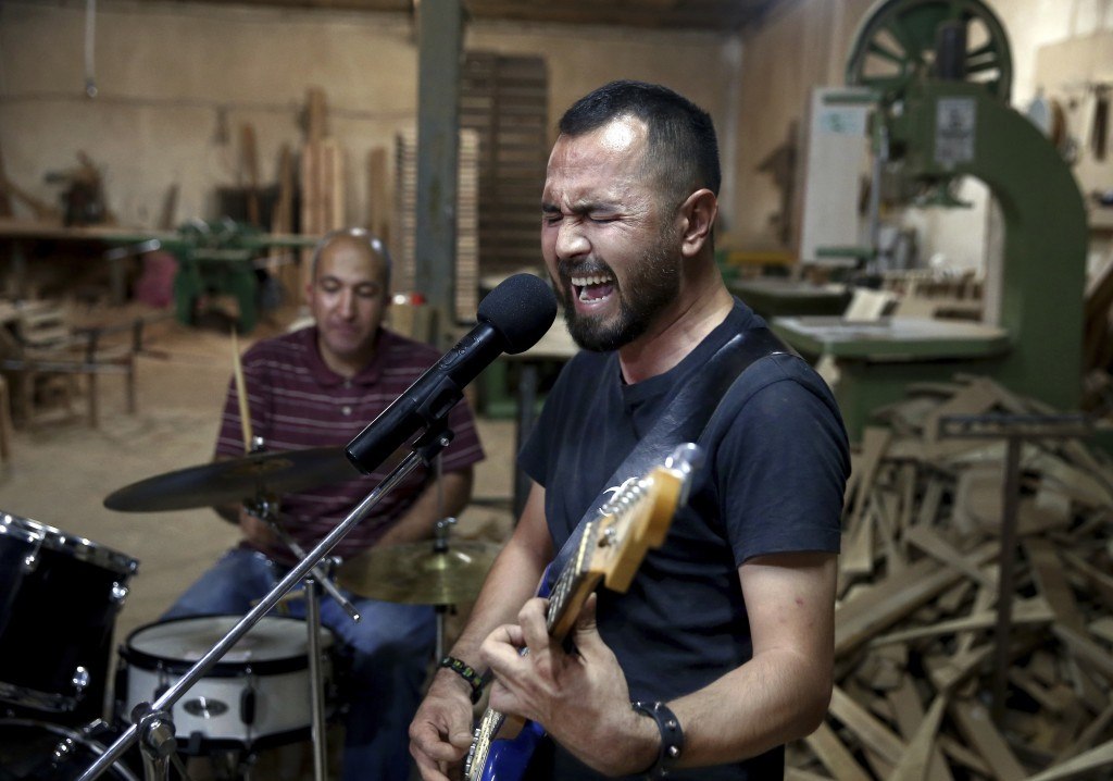 In this July 20, 2018 photo, Afghan musician Hakim Ebrahimi, a member of the Arikayn rock band, plays at a furniture workshop in Eslamshahr, on the ou...