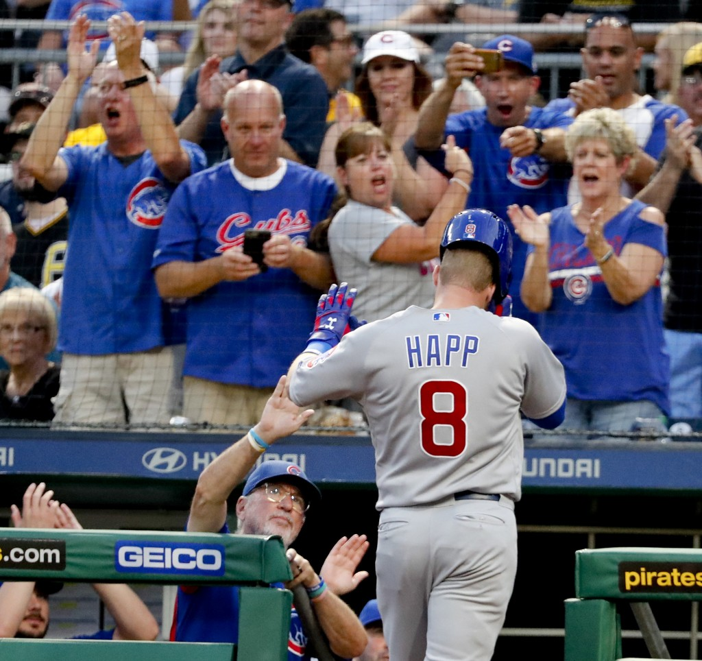 Chicago Cubs' Ian Happ (8) is greeted by manager Joe Maddon, left, and cheering Cubs fans after hitting a solo home run against the Pittsburgh Pirates...