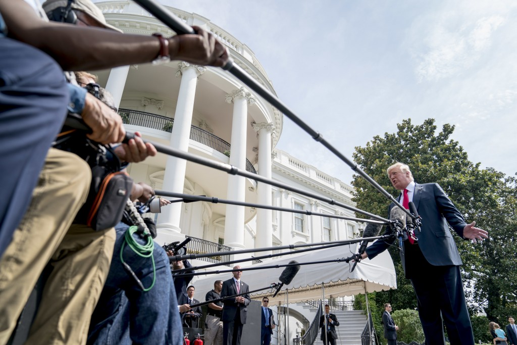 President Donald Trump speaks to members of the media before boarding Marine One on the South Lawn at the White House in Washington, Friday, Aug. 17, ...