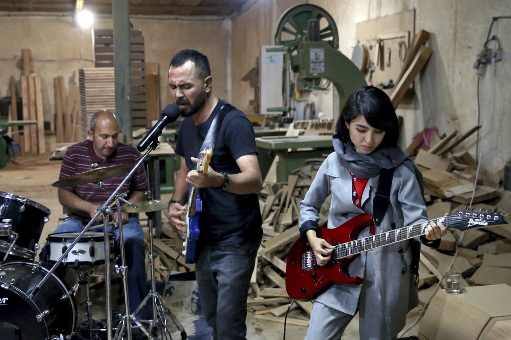 In this July 20, 2018 photo, members of the rock band Arikayn, Afghan musicians Hakim Ebrahimi, center, and Soraya Hosseini, right, play with Kourosh ...