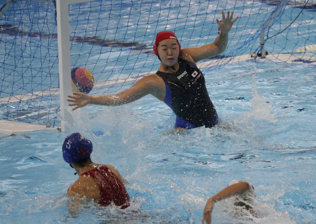 Japan's goal keeper Minami Shioya, center, fails to stop a shot from China's Niu Guannan, left, during their women's tournament group A water polo mat...
