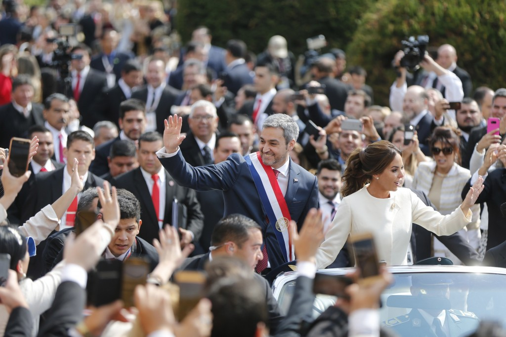 In this Aug. 15, 2018 photo, Paraguay's new President Mario Abdo Benitez rides in an open top car with his wife Silvana Lopez, after his inauguration ...