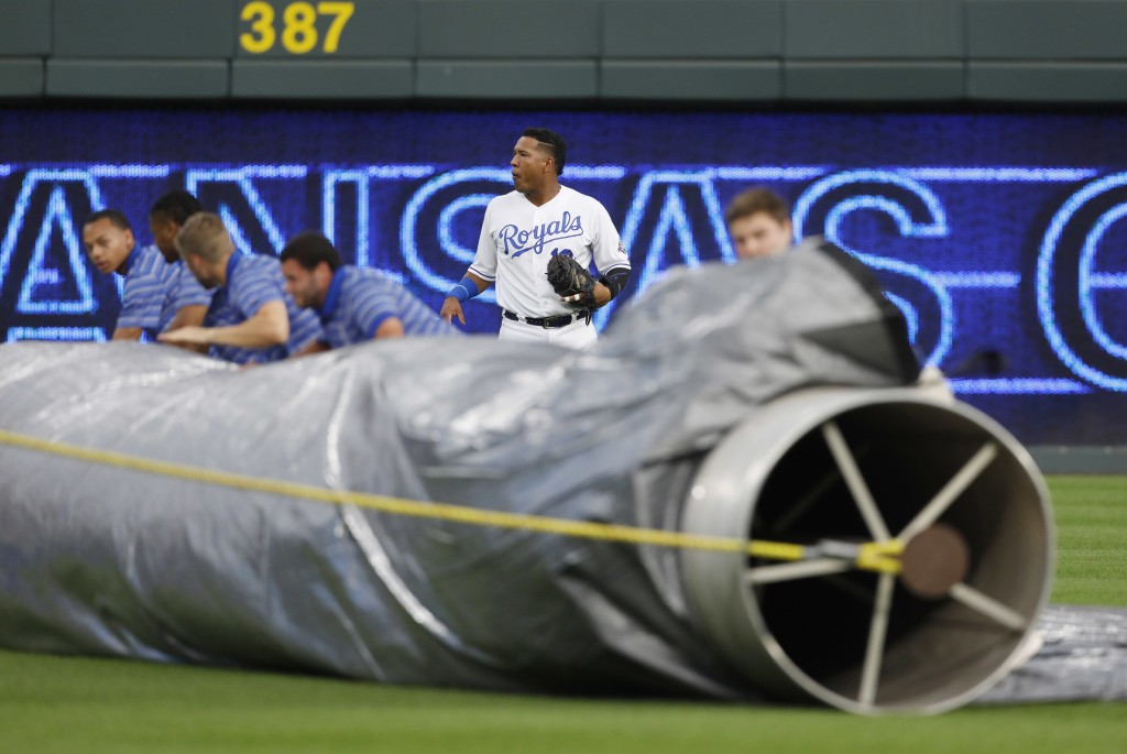 Kansas City Royals catcher Salvador Perez stands nearby as the grounds crew unrolls the infield tarp as a storm approaches before the Royals' baseball...