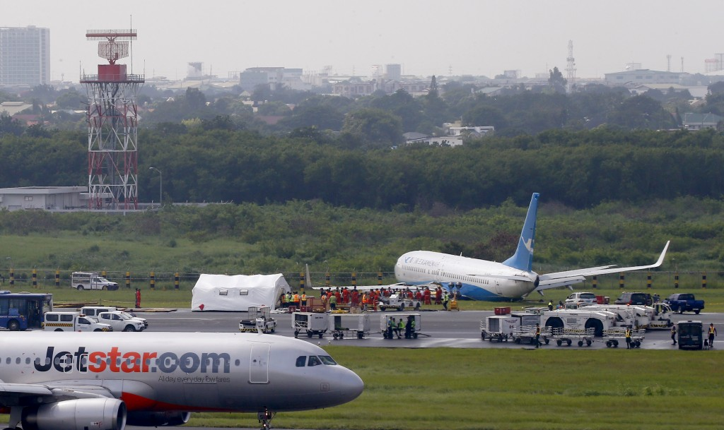 A Jetstar passenger plane taxis upon landing while a Xiamen Air, right, sits on the grassy portion of the runway of the Ninoy Aquino International Air...