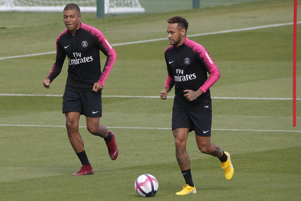 PSG's Neymar, right, and Kylian Mbappe run side by side during a training session at the club training center in Saint Germain en Laye, west of Paris,...