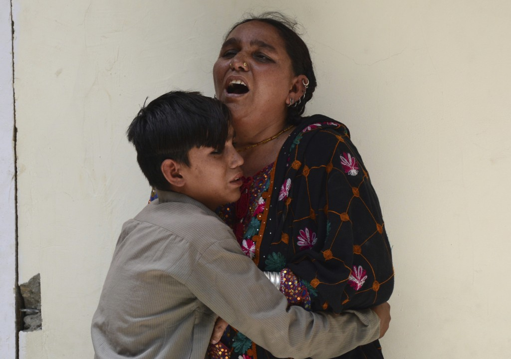 FILE - In this July 25, 2018, file photo, a woman and her son mourn the death of their family member outside a hospital in Quetta, Pakistan were a sui...