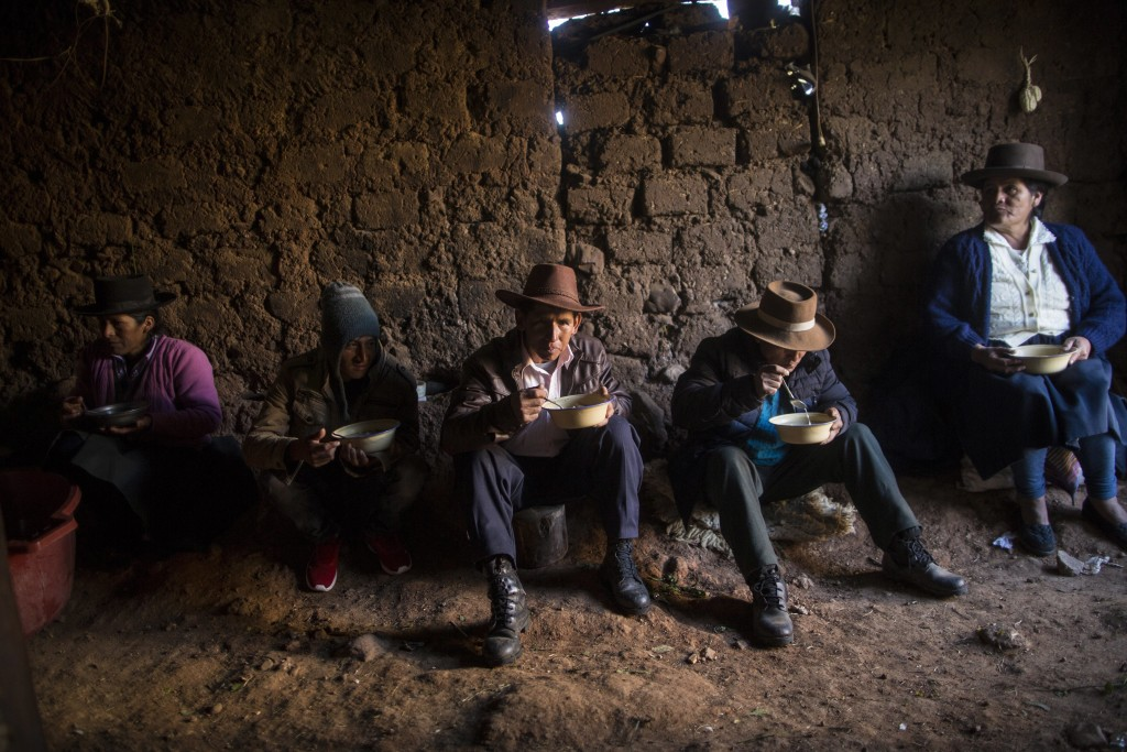 In this Aug. 15, 2018 photo, villagers eat breakfast before giving a proper burial to their loved ones who were killed by Shining Path guerrillas and ...