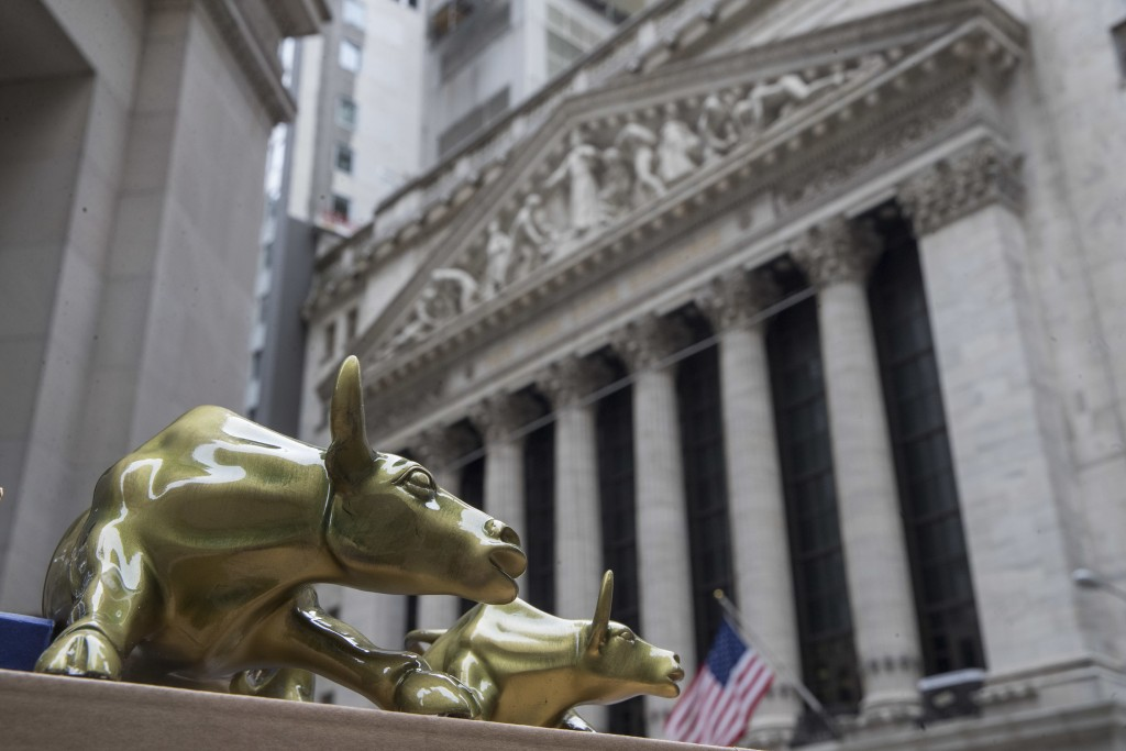 "FILE- In this April 24, 2018, file photo replicas of Arturo Di Modica's ""Charging Bull"" are for sale on a street vendor's table outside the New York S..."