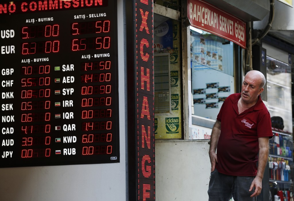 A man checks foreign currency rates at a currency exchange shop in Istanbul, Thursday, Aug. 16, 2018. Beset by a weak currency and tension with the Un...