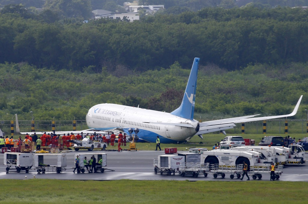 A Boeing passenger plane from China, a Xiamen Air, sits on the grassy portion of the runway of the Ninoy Aquino International Airport after it skidded...