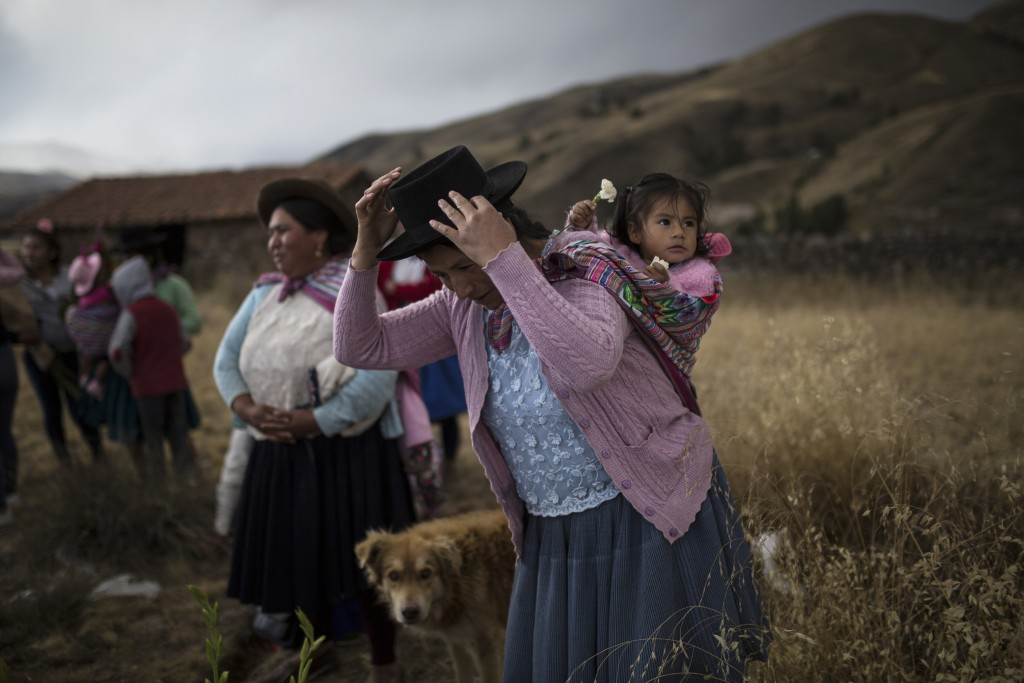 In this Aug. 14, 2018 photo, a woman carrying her daughter prepares to place flowers on the graves of relatives who were killed by the Peruvian army i...