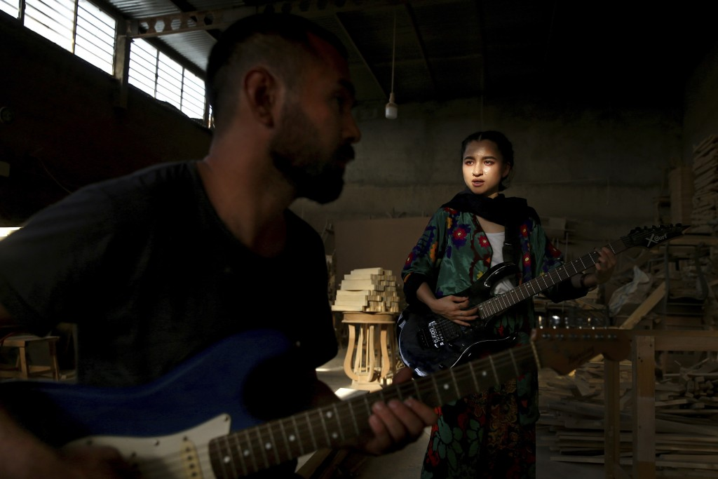 In this July 26, 2018 photo, Afghan musicians Hakim Ebrahimi, left, and Soraya Hosseini, members of the Arikayn rock band, play music at a furniture w...