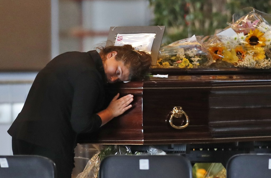 A woman mourns a victim of a collapsed highway bridge, at the Fiera di Genova exhibition center, where some of the coffins are laid in state, in Genoa...