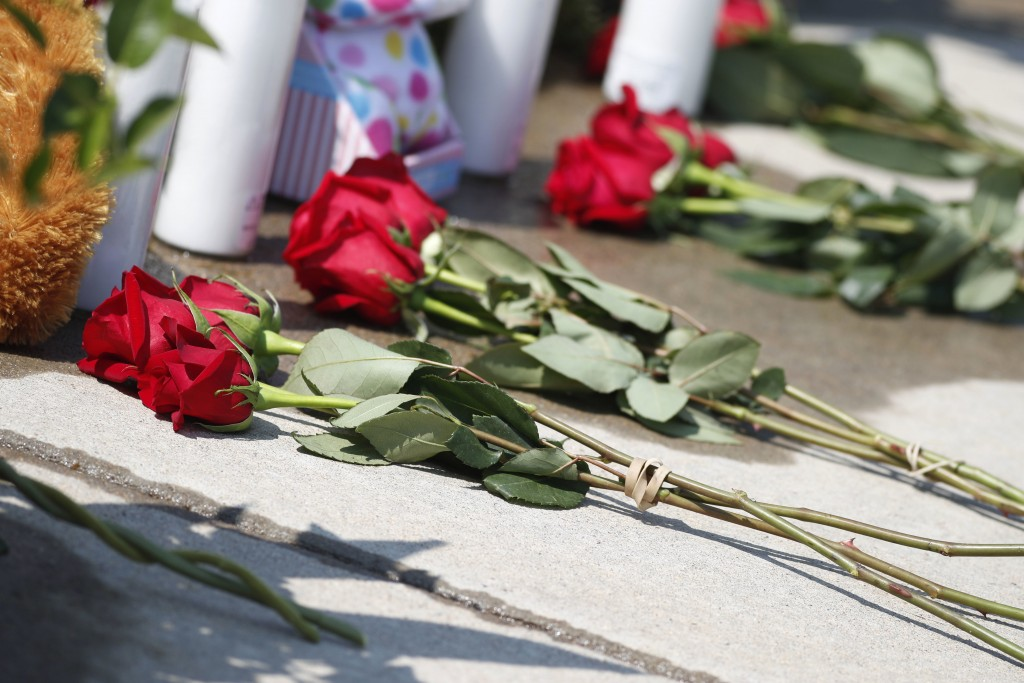 Tributes grow outside the home where a pregnant woman and her two daughters lived Thursday, Aug. 16, 2018, in Frederick, Colo. The woman's husband has...