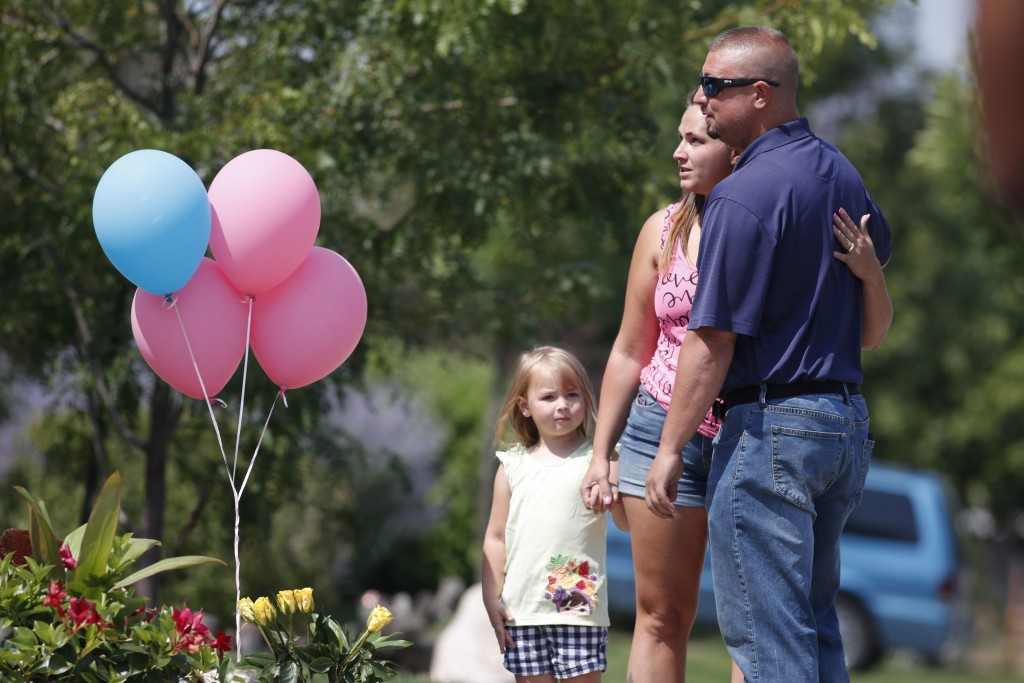 From left, 4-year-old Liberty Bell joins her mother, Ashley, and father Steven as they put a tribute with others outside the home where a pregnant wom...