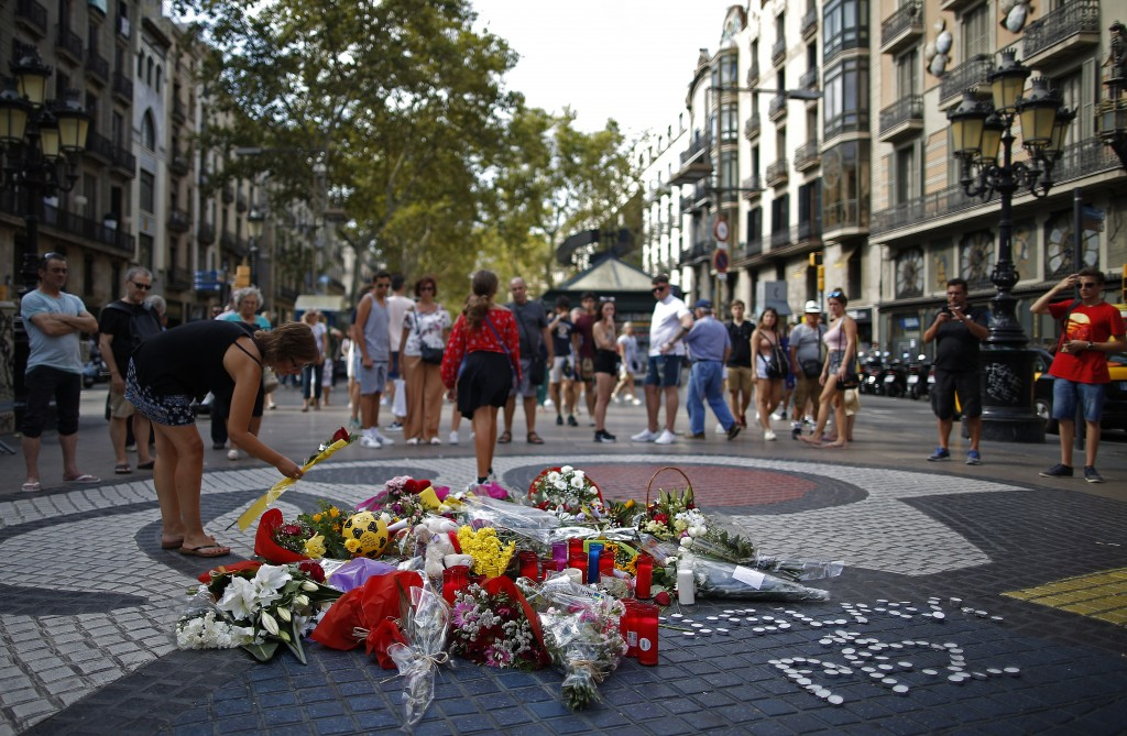 A woman places a flower around a memorial tribute of flowers, messages and candles on Barcelona's historic Las Ramblas in Barcelona, Thursday, Aug. 16...