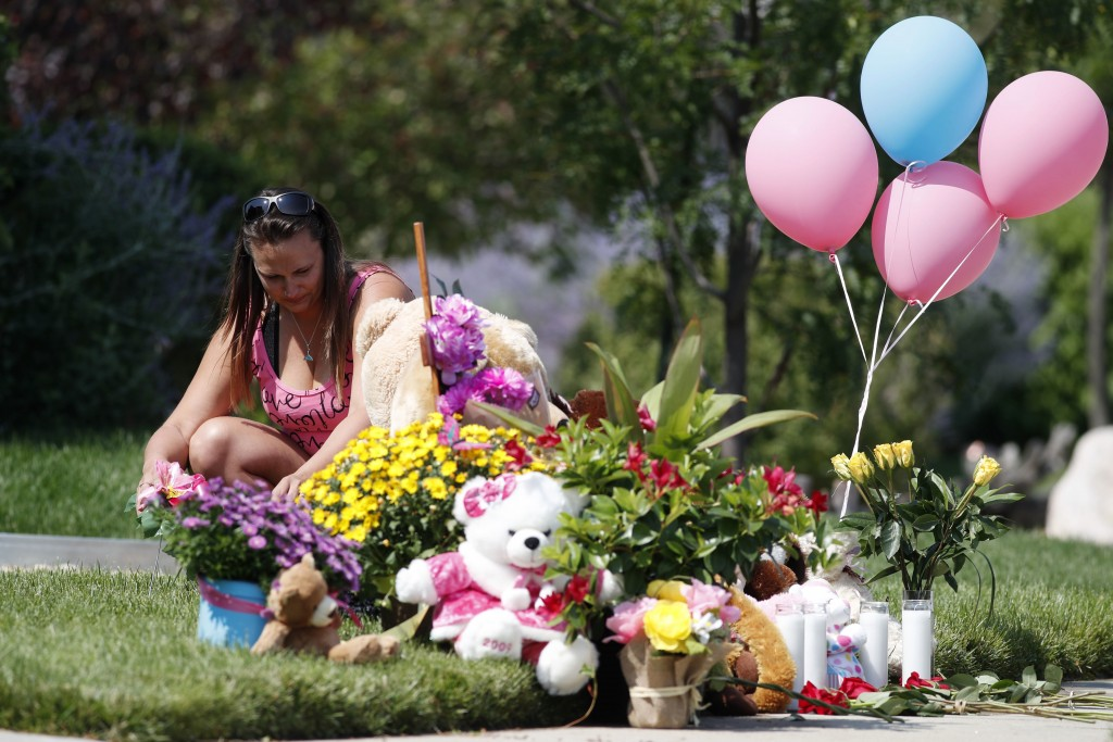 Ashley Bell places flowers with the growing number of tributes outside the home where a pregnant woman and her two daughters lived Thursday, Aug. 16, ...