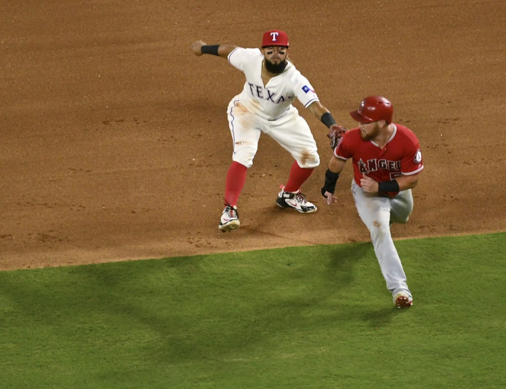 Texas Rangers second baseman Rougned Odor tags out Los Angeles Angels' David Fletcher for the third out of a triple play on a ground ball by Fletcher ...