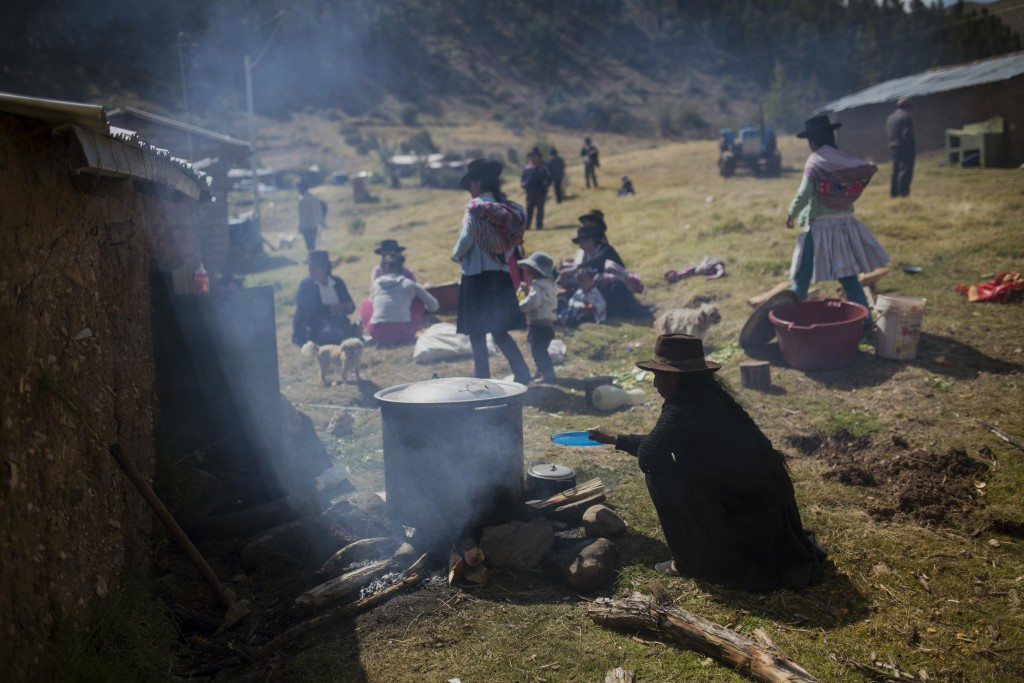 In this Aug. 15, 2018 photo, the relatives of villagers who were killed by the Shining Path guerrillas and the Peruvian army in the 1980s cook lunch a...