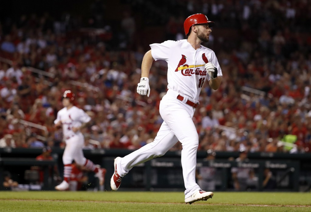 St. Louis Cardinals' Paul DeJong, right, heads to first for a single as teammate Tyler O'Neill jogs in to score during the sixth inning of a baseball ...