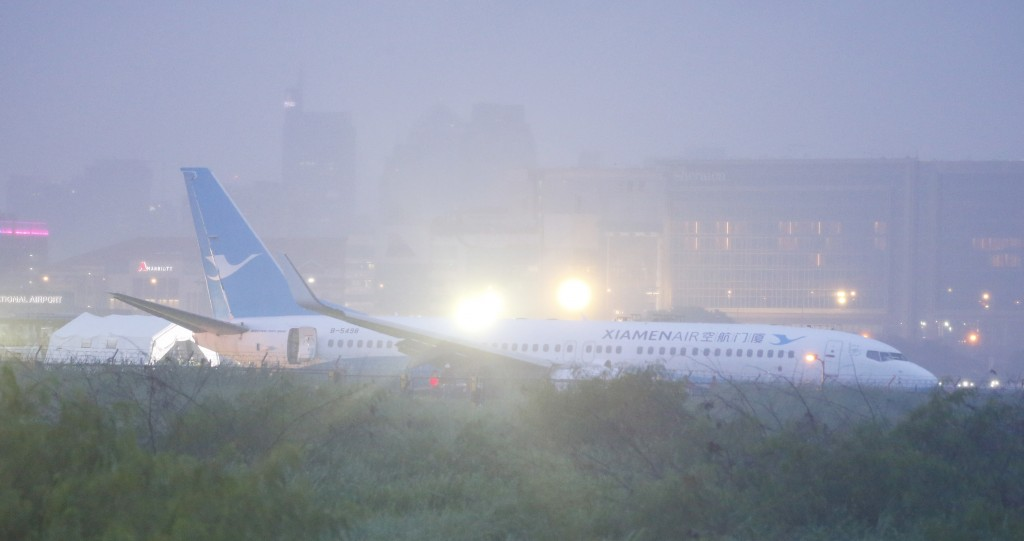 A Boeing passenger plane from China, a Xiamen Air, lies on the grassy portion of the runway of the Ninoy Aquino International Airport after it skidded...