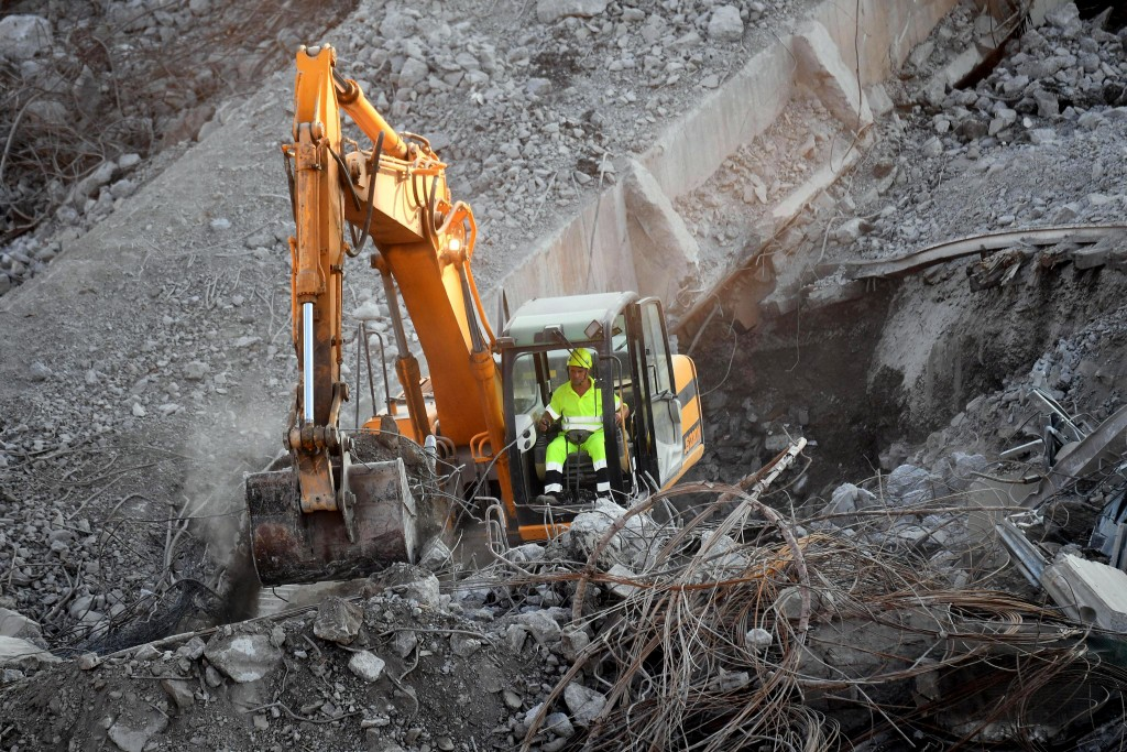 A caterpillar removes debris of the collapsed Morandi highway bridge in Genoa, Italy, Thursday, Aug. 16, 2018. Italian authorities have lowered the de...