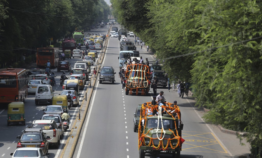 The body of former Indian prime minister Atal Bihari Vajpayee, center, is taken in full state honor to the Bharatiya Janata party office for people to...