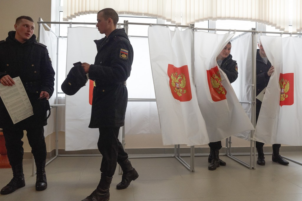 FILE - In this March 18, 2018 file photo Russian military sailors exit a polling booth as they prepare to cast their ballots at a polling station duri...